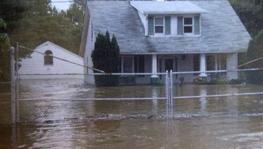 Floodwaters from a storm surround a Marshallton home in 2004, during one of the incidents that prompted a more-than decade-long effort to rewrite state stormwater and erosion-control regulations.