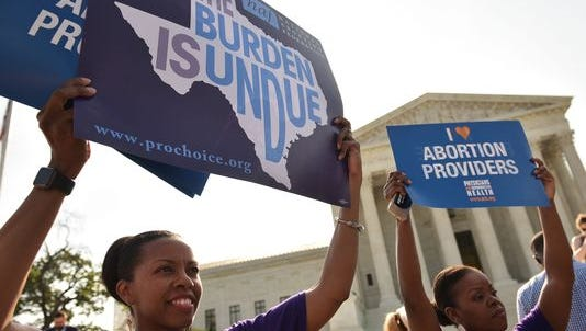 Abortion rights activists hold signs outside of the Supreme Court ahead of its ruling on abortion clinic restrictions on June 27.