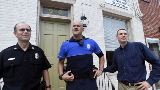 Retired Chambersburg Police Chief David Arnold, left, Mayor Darren Brown, right, and a Chambersburg police officer, stand in front of the now former borough police substation on West Washington Street. The substation is now closed, but the department is keeping its community policing effort going with other initiatives.