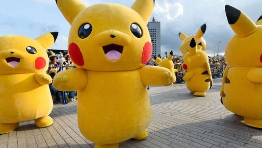 """Dozens of people dressed as Pikachu, the famous character from Nintendo's video game software Pokemon, dance with fans as the final of a nine-day """"Pikachu Outbreak"""" event takes place to attract summer vacationers in Yokohama, in suburban Tokyo, on Aug. 16, 2015."""