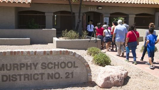 Parents and children walk into the Murphy Elementary School District offices in Phoenix on July 13, 2016.