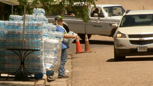 Volunteers hand out cases of bottled water to residents in Hugo, Colo.