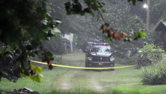 A sheriff's car sits in a driveway with police tape across it Tuesday in the 500 block of Poes Run Road.