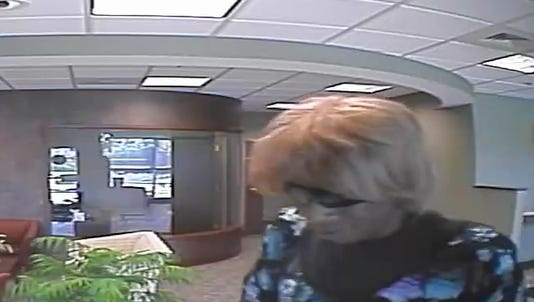 In this surveillance photo from an earlier York Township bank robbery, a man is seen wearing a wig and dress.