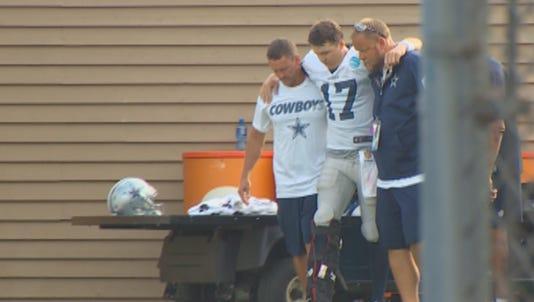 Dallas QB Kellen Moore is helped off the field after suffering a broken leg.