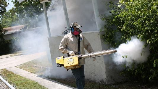 A Miami-Dade County mosquito control inspector sprays pesticide to control the Zika virus outbreak.