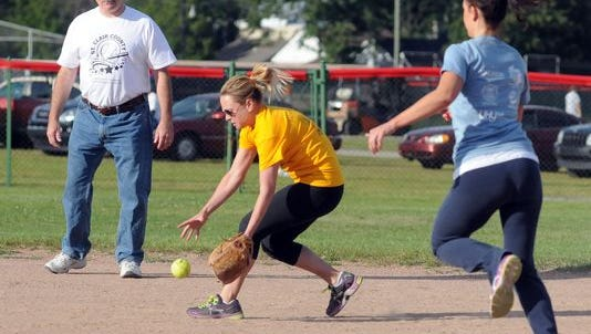 Judge John Tomlinson watches as Crime Catcher Melissa Keyes fields the ball and Talmer Bank and Trust's Jackie Hanton runs to second base during the charity softball game to benefit the St. Clair County Child Abuse and Neglect Council at Memorial Stadium in 2013.