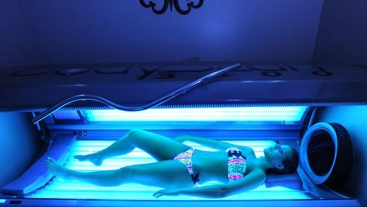 A woman lays in a tanning bed