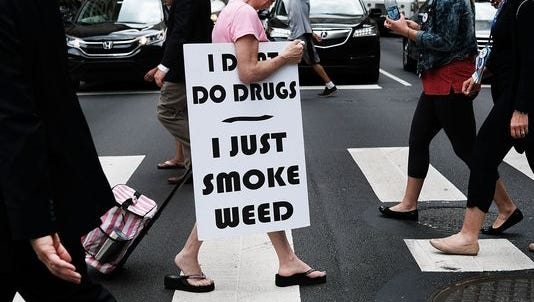 A woman walks with a sign supporting legalizing marijuana during the Democratic National Convention in Philadelphia.