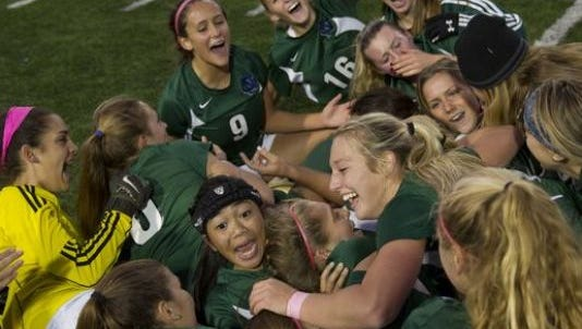The Colts Neck girls soccer team celebrates winning the first state title in school history on Nov. 21, 2015 at Kean University