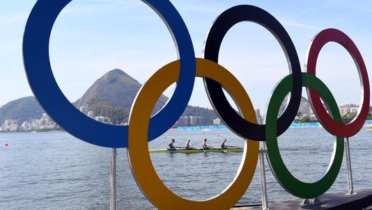 Rowers are seen through the Olympic rings as seen from Copacabana Beach on Aug. 6.