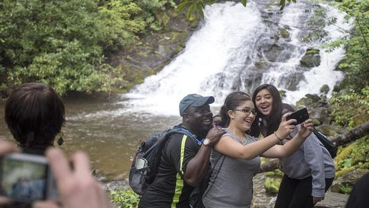 Great Smoky Mountains National Park Superintendent Cassius Cash jumps in a photo with Cherokee middle school students while stopping a waterfall in April 22 while on a hike through the Deep Creek.