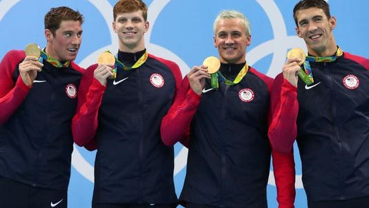 U.S. swimmers show off Olympic gold, which translates into tax dollars.