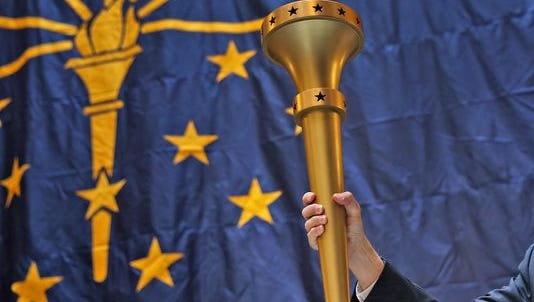 Indiana Gov. Mike Pence holds up the Indiana bicentennial torch during the Statehood Day Celebration at the Statehouse on Dec. 11, 2015. The event began the celebration of Indiana's 199th birthday.