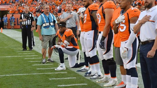 Denver Broncos inside linebacker Brandon Marshall (54) kneels during the national anthem before the game against the Carolina Panthers at Sports Authority Field at Mile High.