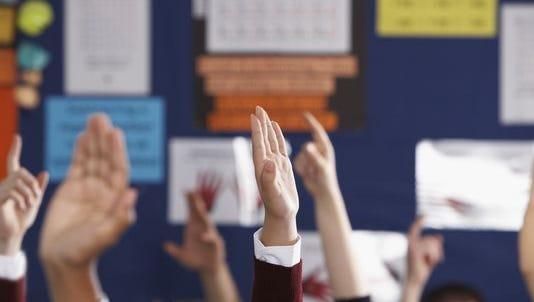Stock photo of students raising hands.