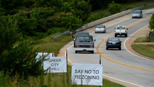 Cars drive past anti-rezoning signs along Brushy Creek Road on Tuesday, July 12, 2016.