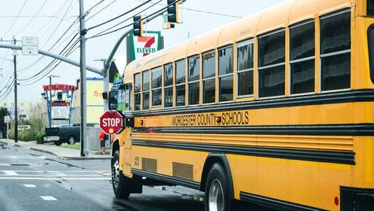 A Worcester County school bus on a stop, with its stop arm displayed.