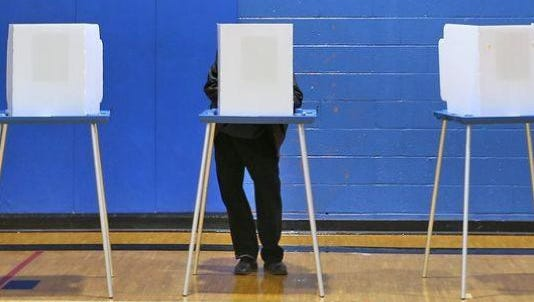 A voter casts his ballot at the Douglass Park Community Center on Election Day in November 2014.