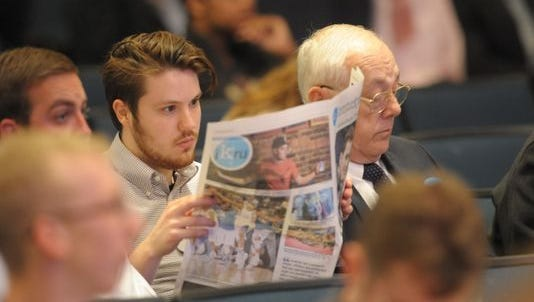 In this file photo, Judah Taylor, a former Kentucky Kernel staffer, reads the newspaper during a memorial for Jonathan Krueger, a UK student and Kernel staffer who was killed in April 2015. The newspaper has won a Pacemaker Award.