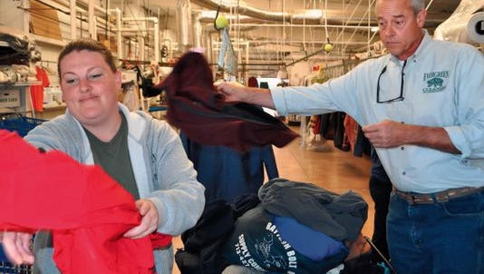 Bart Byars of Evergreen Cleaners sorts through coats to be cleaned during last year's coat drive.