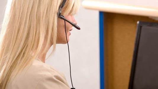 A receptionist working at a computer with a headset