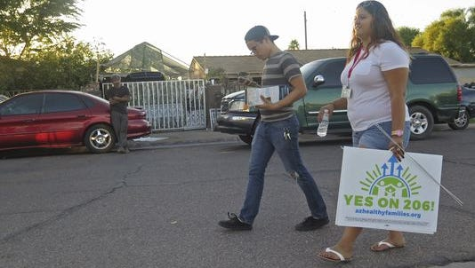 Workers with Living United for Change in Arizona go door-to-door urging voters to approve a minimum wage increase earlier this year. Arizona was one of four states to approve an increase in the minimum wage to at least $12 an hour on Tuesday.