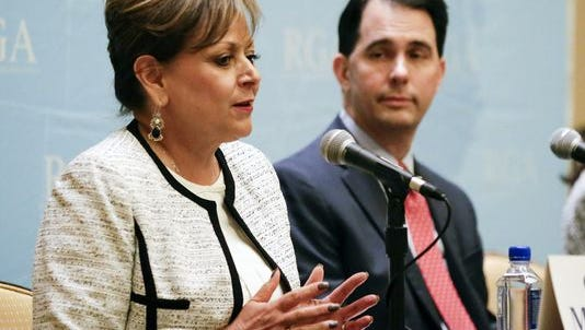 New Mexico Gov. Susana Martinez, left, speaks during a news conference while Wisconsin Gov. Scott Walker looks on, at the Republican Governors Association annual conference, Tuesday, Nov. 15, 2016, in Orlando, Fla.