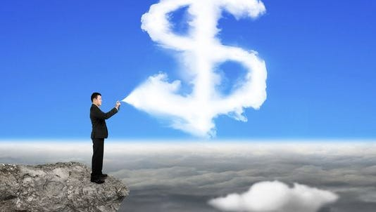 Businessman spraying dollar sign shape cloud paint on the cliff with cloudscape background.