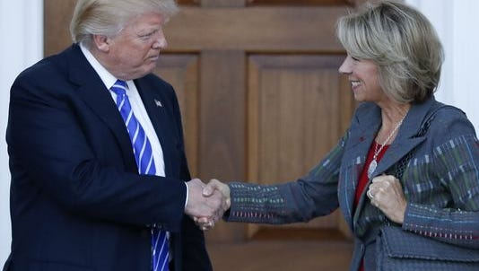 Donald Trump and Betsy DeVos shake hands. Assistant Professor Elizabeth Wheat from UW-Green Bay says Trump's engagement on social media could change the face of diplomacy.