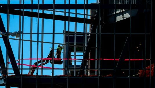 A construction worker is seen at the site of MSUFCU's headquarter's expansion. About 50 employers in the Lansing area will be hiring up to 1,300 people in the next year in construction and manufacturing jobs.