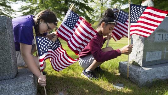 Grace Williams, left, and Selena Spanakis, place flags at the graves of veterans for Memorial Day in 2016. Students from St. Rose of Lima Elementary School, in Jackson Township, placed flags at Holy Savior Cemetery in Manchester Township.