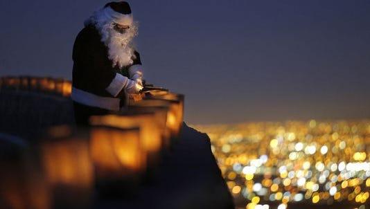Santa Claus lights luminarias along Scenic Drive in 2015.