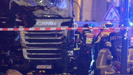 Rescue workers inspect the scenes and the truck that crashed into a Christmas market, close to the Kaiser Wilhelm memorial church in Berlin, Dec. 19, 2016.