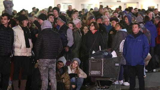 People wait in line for NJ Transit buses after the Jersey Gardens Mall was evacuated on one of the busiest days of the year after a fight broke out Dec. 26, 2016.