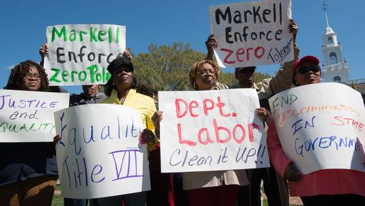 """Demonstrators hold signs in front of Legislative Hall in Dover in March to demand Governor Jack A. Markell take action against what they call """"racist"""" supervisors in state government. A Markell-contracted consultant on Friday published a report on discrimination in state government."""