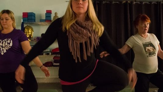 People practice yoga at Studio Exhale, 103 N. High St.