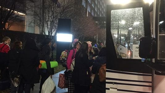People heading to the nation's capital for Saturday's Women's March on Washington board a charter bus Friday night outside the MGM Grand casino in Detroit. Other would-be marchers were stood up by a charter company, though some made alternative arrangements, like sharing a ride.
