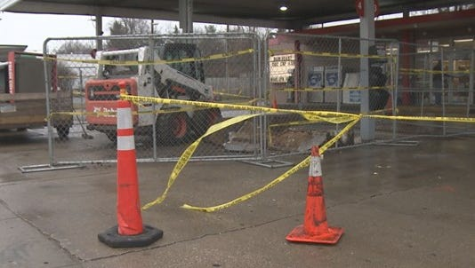 Police say a 74-year-old woman reversed into a gas pump, causing it to ignite catch a man on fire.