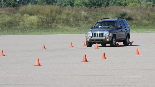 A high school student attempts to drive around orange cones during a 2014 distracted-driving class sponsored by the Livingston County Sheriff's Department and held at the FT Techno of America track in Handy Township.