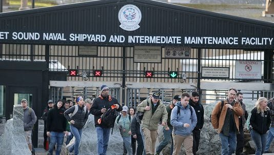 Employees at the Puget Sound Naval Shipyard and Intermediate Maintenance Facility leave the main gate.
