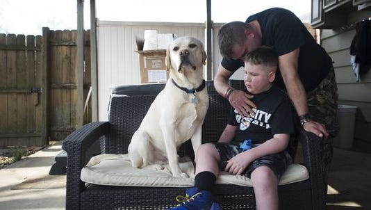 Bill Kohler comforts his son, Ayden Ziegler-Kohler, 10, as he sits on their patio with his dog, Zuko. Ayden, who has a rare childhood cancer and limited mobility, was upset after seeing other kids out playing on the playground.