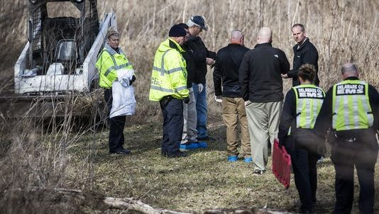 Investigators at the scene of a Feb. 14 slaying. A Muncie man's body was found in a field along Inlow Spring Road.