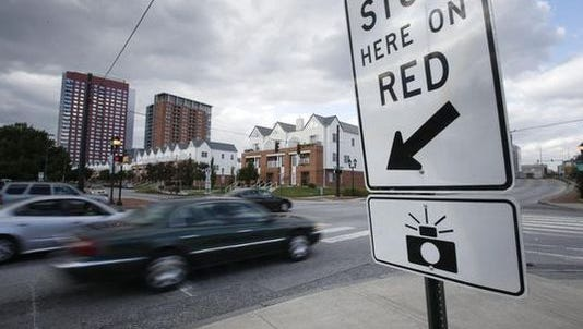 Vehicles pass a red-light camera on Walnut Street at A Street in Wilmington in 2015.  Drivers ticketed for making a right turn against a red light by the cameras will receive a refund.
