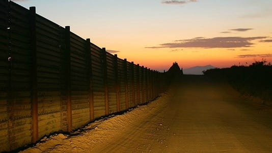 A US-Mexico border fence is illuminated by car headlights at sunset.