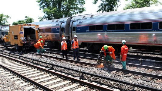 A train passes as Metro-North employees finish pot welding a rail near the Hastings-on-Hudson station.