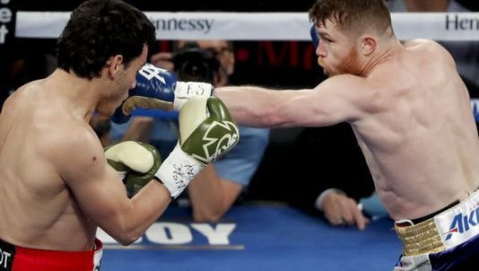 Canelo Alvarez, right, of Mexico, hits Julio Cesar Chavez Jr., of Mexico, during their catch weight boxing match, Saturday, May 6, 2017, in Las Vegas.(AP Photo/Isaac Brekken)