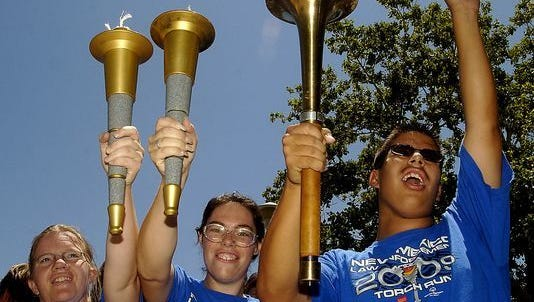 Special Olympics athletes carry torches in the 2009 Special Olympics Torch Run.