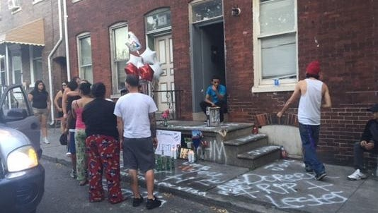 A photograph from the York Daily Record website on Monday shows residents gathering near the place where Lester Cortes-Cotto was attacked on the first block of East Maple Street last Sunday morning.