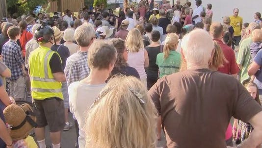 Hundreds of people gathered at the entrance of an alleyway in southwest Minneapolis to mourn the woman who was shot and killed by police there on Saturday night.